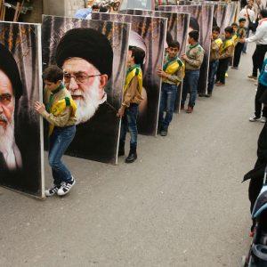 Giovani sostenitori di Hezbollah trasportano i ritratti di Ruhollah Khomeini, fondatore della Repubblica Islamica dell'Iran e Ali Khamenei, attuale Guida suprema dell'Iran, nella città libanese di Kfar Hatta (MAHMOUD ZAYYAT/AFP/Getty Images)